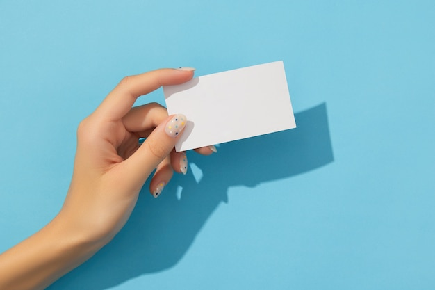 A mão de uma mulher bem cuidada segurando um cartão de visita sobre fundo azul