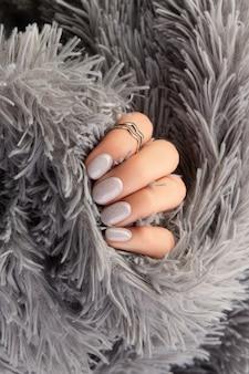 A mão de uma mulher bem cuidada segurando um tecido cinza peludo
