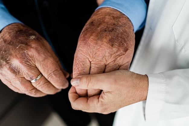A mão de uma mulher caucasiana segura afetuosamente a mão enrugada de um homem mais velho.