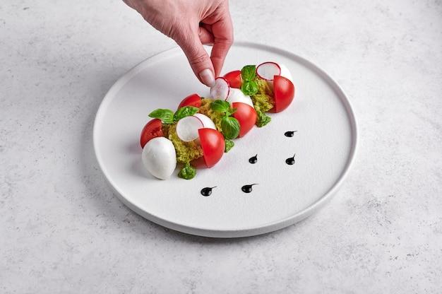 A mão de uma mulher coloca a fatia de rabanete em uma deliciosa salada caprese italiana com tomates maduros, manjericão fresco e queijo mussarela
