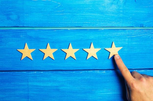A mão de uma mulher coloca a quinta estrela. o status de qualidade é cinco estrelas. uma nova estrela, conquista