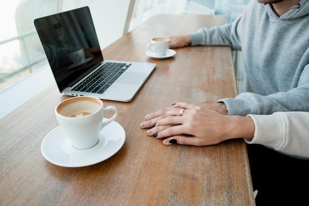 A mão de uma mulher com anel de ouro cobre a mão do homem. conceito de encontro romântico. laptop moderno e duas xícaras de café vazias na mesa de madeira. estilo casual. casal heterossexual, bom tempo para gastar.