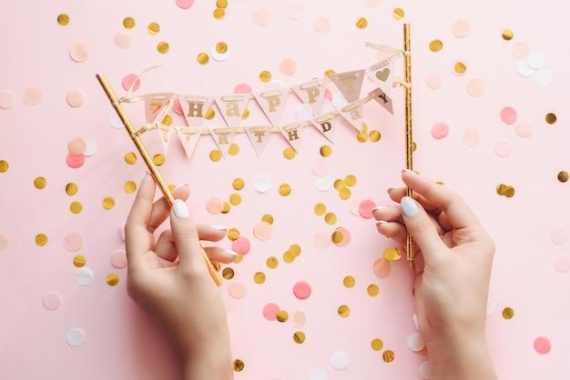 A mão de uma mulher com manicure pastel mantém um pequeno banner feliz aniversário. saudações de feliz aniversário em fundo rosa com confete