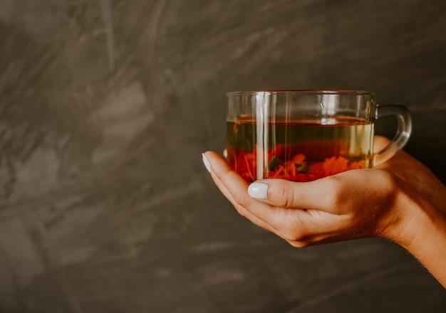 A mão de uma mulher com pele clara e manicure branca nas unhas segura uma grande xícara de cerâmica transparente com chá feito de flores.