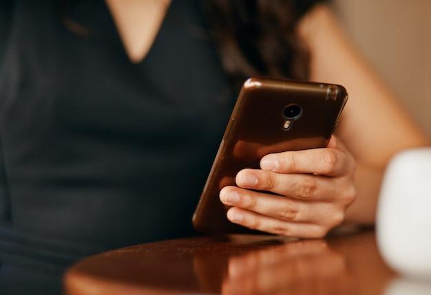 A mão de uma mulher com um close-up de smartphone