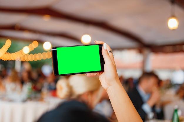 A mão de uma mulher com um smartphone fotografa a tela em branco da festa