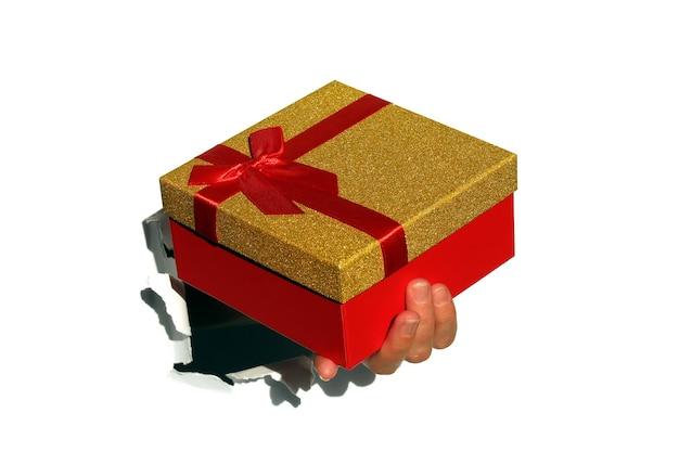 A mão de uma mulher com uma caixa de presente vermelha foi enfiada por um buraco no papel branco