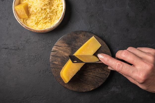 A mão de uma mulher com uma faca corta um pedaço de parmesão em uma tábua de madeira