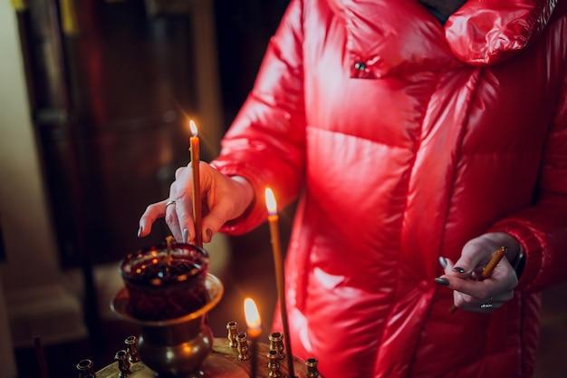 A mão de uma mulher com uma jaqueta vermelha coloca uma vela da igreja.