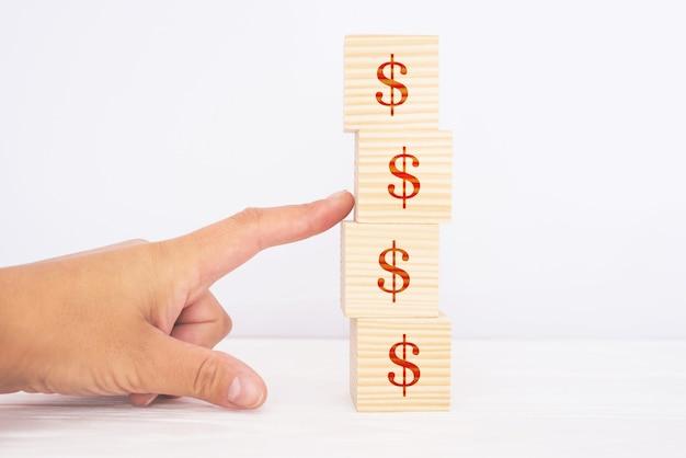 A mão de uma mulher destrói uma pirâmide de cubos de madeira com um símbolo de dólar. o conceito de queda financeira, crise, risco.