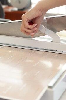 A mão de uma mulher em close-up pressiona o cabo de uma guilhotina manual que corta brochuras ou folhetos uma faca de aço em movimento