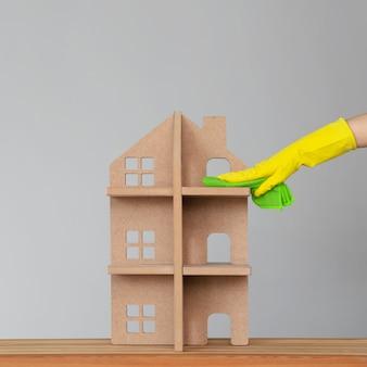 A mão de uma mulher em uma luva de borracha lava a casa simbólica com um pano verde. o conceito de limpeza de primavera e limpeza.