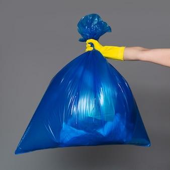 A mão de uma mulher em uma luva de borracha mantém um saco de plástico azul cheio de lixo.