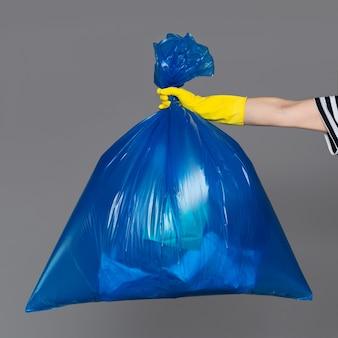 A mão de uma mulher em uma luva de borracha segura um saco plástico azul cheio de lixo.