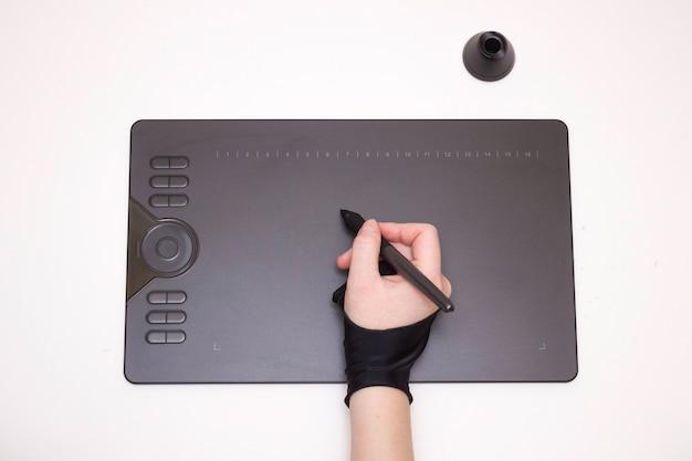 A mão de uma mulher em uma luva especial desenha em um fundo branco de tablet gráfico isolado