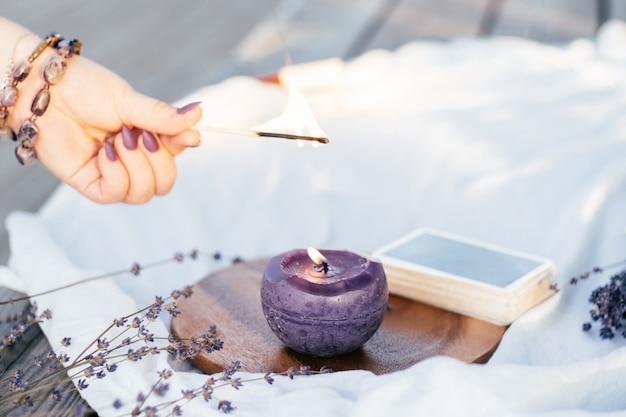 A mão de uma mulher em uma pulseira com unhas compridas roxas acende uma vela com um fósforo, ao lado do baralho de cartas e flores de lavanda na superfície branca e de madeira
