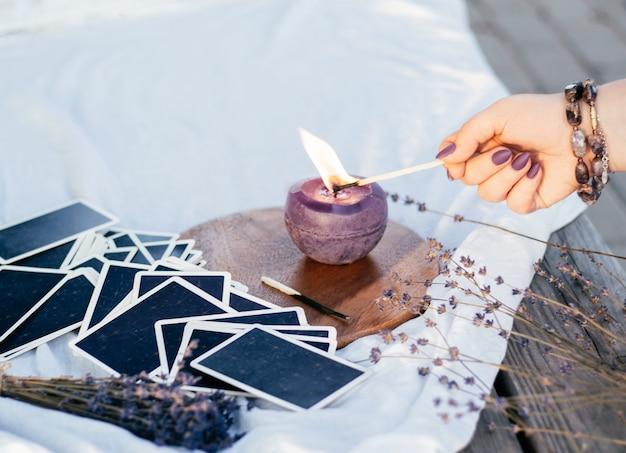 A mão de uma mulher em uma pulseira com unhas compridas roxas acende uma vela com um fósforo, ao lado do baralho de cartas e flores de lavanda
