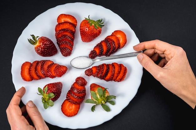 A mão de uma mulher em uma visão aérea de morangos naturais em um prato branco