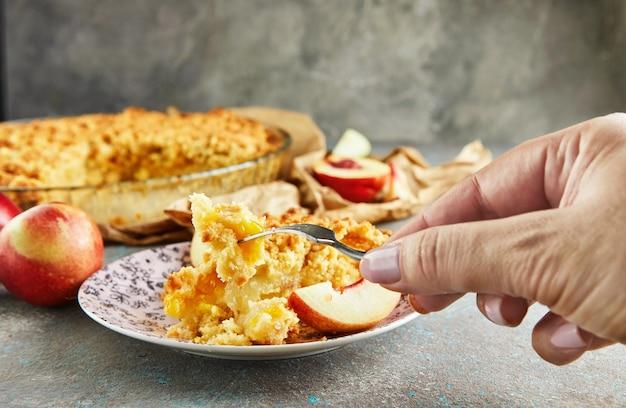 A mão de uma mulher espeta um pedaço de torta com pêssegos e peras em um garfo