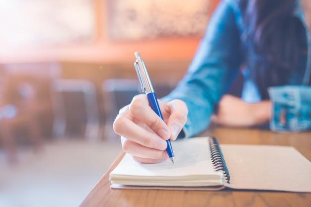 A mão de uma mulher está escrevendo no bloco de notas vazio da espiral com uma pena.