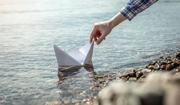 A mão de uma mulher está lançando um barco de papel branco nas águas cristalinas do mar com um fundo pedregoso.