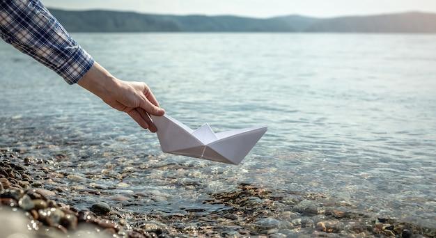 A mão de uma mulher está lançando um barco de papel nas águas claras de um lago baikal com fundo pedregoso