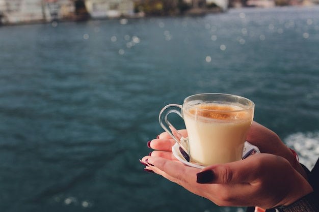 A mão de uma mulher está segurando uma xícara branca de bebida quente com leite com canela, chamada turca salep sahlep, no fundo da água ondulante e da enevoada torre da donzela à distância, istambul.