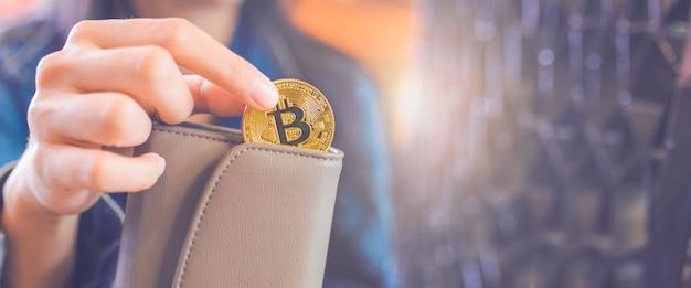 A mão de uma mulher está tirando uma moeda de bitcoin de uma carteira.
