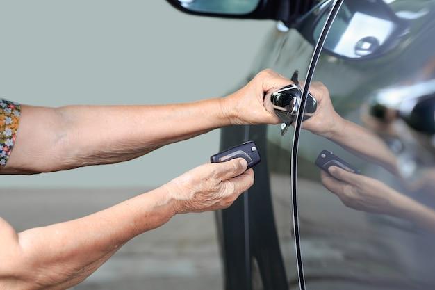 A mão de uma mulher idosa abre o carro nos principais sistemas de alarme de carro