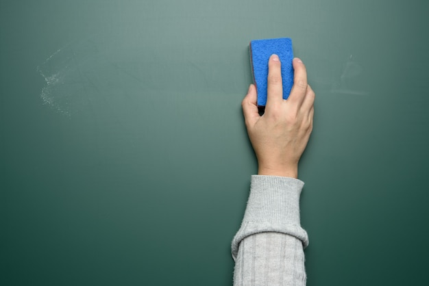A mão de uma mulher limpa um quadro de giz verde com uma esponja azul, close-up