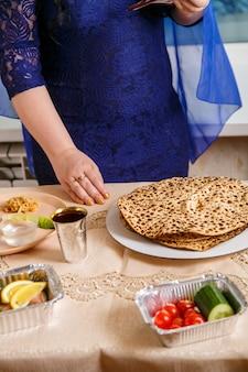 A mão de uma mulher na mesa do seder da páscoa está comendo um choroset