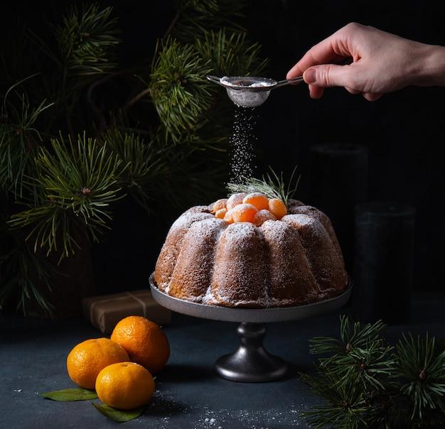 A mão de uma mulher polvilha açúcar de confeiteiro em um bolo de natal de tangerina. imagem escura e de humor