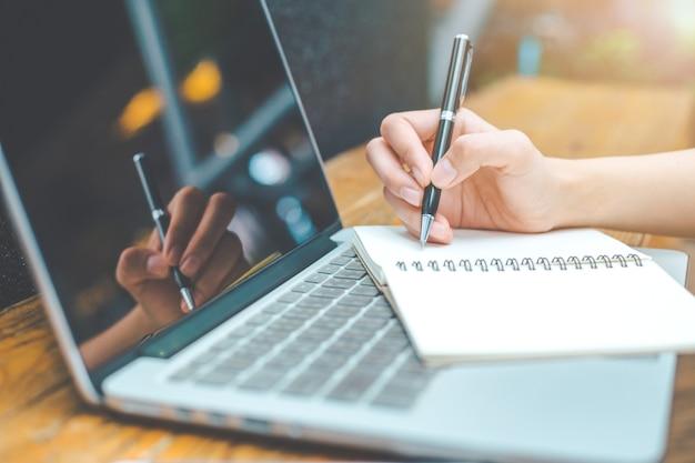 A mão de uma mulher que trabalha em um computador portátil e que escreve em um bloco de notas com uma pena no escritório.