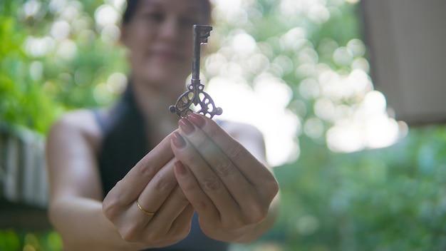 A mão de uma mulher segura a chave ao ar livre. conceito de esperança, fé, cristianismo, religião.