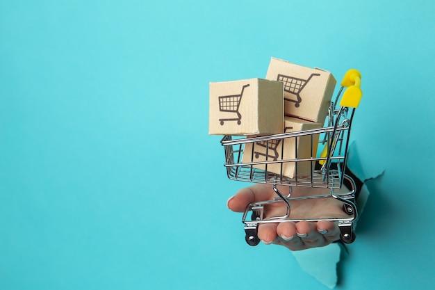 A mão de uma mulher segura através de um buraco um carrinho de compras com caixas de entrega em um fundo de papel. conceito de vendas.