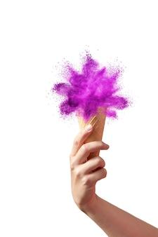 A mão de uma mulher segura o cone do waffle com respingos de pó abstrato colorido como um sorvete doce em uma parede branca, copie o espaço.