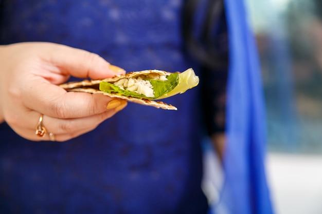 A mão de uma mulher segura pão ázimo e maror em sua mão. foto horizontal
