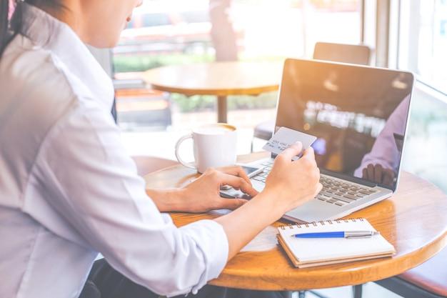 A mão de uma mulher segura um cartão de crédito e usa um computador laptop para fazer compras online.