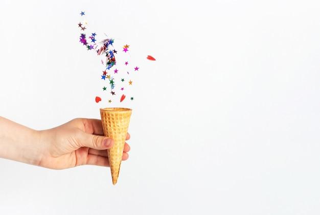 A mão de uma mulher segura um cone de waffle e confete caindo no fundo branco
