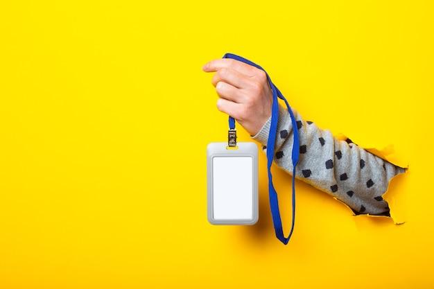 A mão de uma mulher segura um crachá em branco sobre um fundo amarelo rasgado.