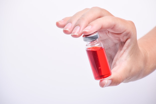 A mão de uma mulher segura um frasco ou ampola médica. vacina. a ampola com o remédio. medicação para injeção.