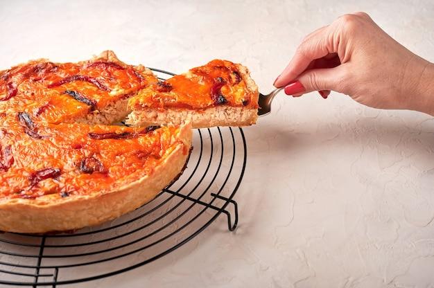A mão de uma mulher segura um pedaço de torta de quiche caseira com tomate seco na omoplata