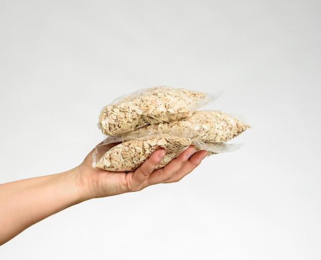 A mão de uma mulher segura um saco transparente com fundo branco de aveia