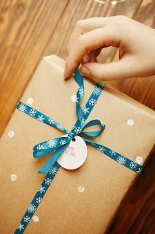 A mão de uma mulher segura uma fita azul com flocos de neve da caixa de presente de ano novo