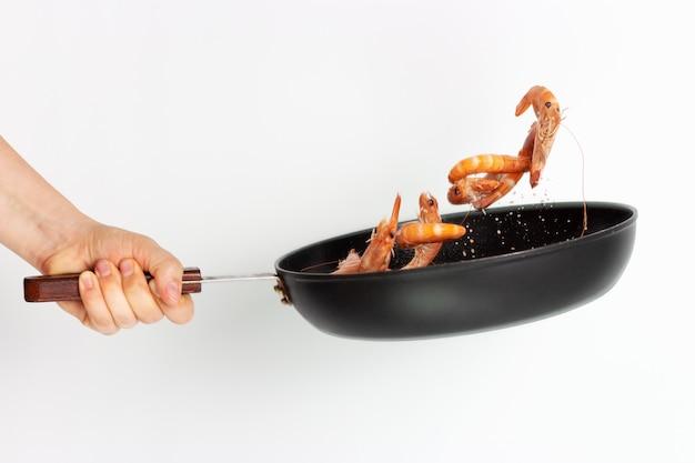 A mão de uma mulher segura uma frigideira e frita camarão em uma superfície branca