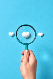 A mão de uma mulher segura uma grande lupa acima da figura de gesso do coração em conjunto
