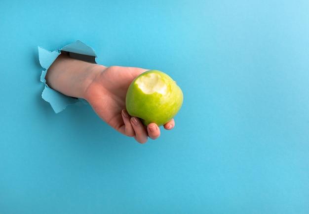 A mão de uma mulher segura uma maçã mordida através de um buraco no papel sobre um fundo azul