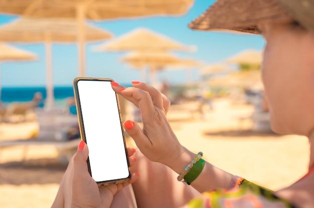 A mão de uma mulher segurando um celular preto com uma tela em branco enquanto se deita na praia