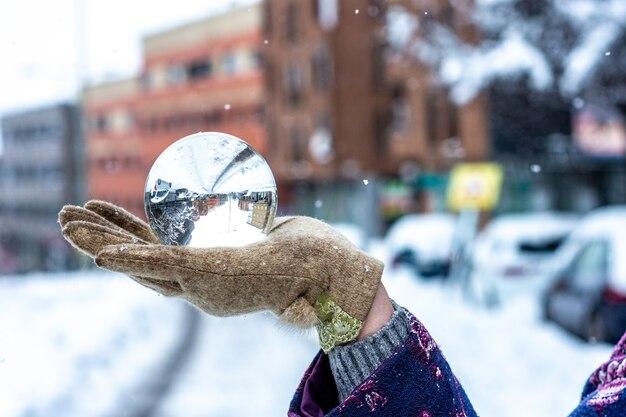 A mão de uma mulher segurando uma bola de cristal na avenida principal. paisagem urbana de neve.