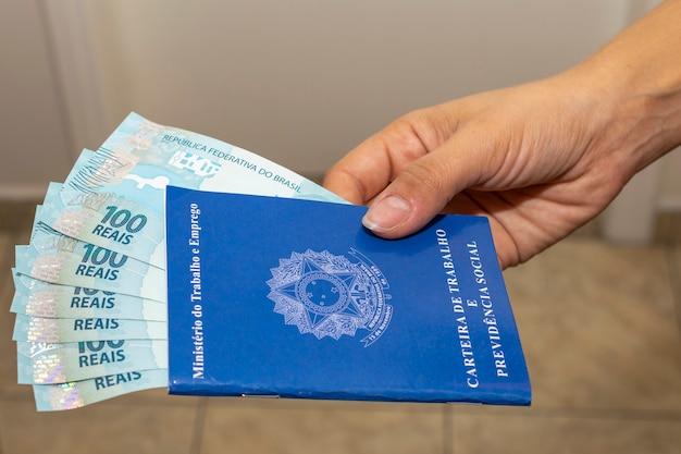 A mão de uma mulher segurando uma carteira de trabalho com notas de dinheiro brasileiras